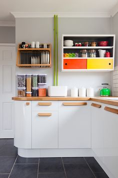 A kitchen with both form and function from colour + shape. Oak door pulls add a bespoke feel to simple white cupboards.