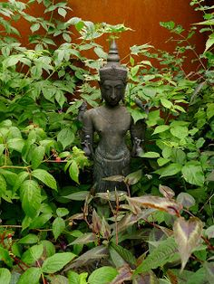 A candle illuminates a Khmer Buddha in a niche in my garden       Ganesha peers from a moss encrusted niche in my garden    Winter in the...