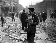 World War II, 13th February 1945, London, England, A Rescue worker holds a cat amidst the devastation and rubble caused by a V-bomb launched by a Nazi raid in Judd Street (Photo by Popperfoto/Getty Images)