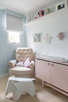 Decoração de apartamento com quarto de bebê em tons pastel, cômoda rosa, poltrona bege e adornos.