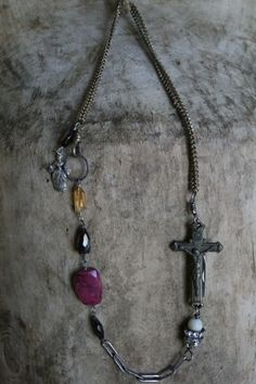 This is a fabulous piece that is also great to layer with other necklaces. Gemstones,vintage brass chain, sterling silver chain, vintage rhinestones and a very hard to find vintage cross that is actually a knife create a one of kind piece. The knife reads God Protect on the back side. This piece measures approx.24 in length.