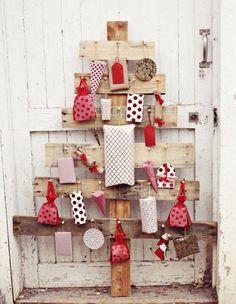 Weihnachtsbaum aus alten Holzbrettern und darauf kleine Geschenk hängen