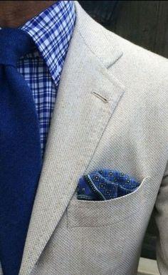 Light grey jacket, blue plaid shirt, blue tie