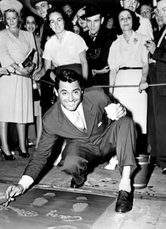 CARY GRANT leaves his prints in cement at Grauman's Chinese Theatre on July 16, 1951.