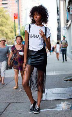 10 Looks para quem ama franjas. T-shirt branca gráfica, saia de couro com franjas, tênis preto