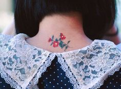 Red camellia tattoo on the back of the neck.