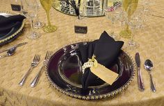 A Gatsby-styled placesetting: Vintage has turned masculine so we muted the glitter accents and brought in black for a more defined contrast. There is still texture but with some hard, clean lines to perpetuate the masculinity in the table. Shown: Black beaded acrylic chargers under a gold beaded glass charger; black matte satin napkin with ivory pearl wristlet used as napkin ring (could be a guest gift!).  #dressyourday FestivitiesMN.com