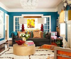 A richer blue on the walls brings out the room's substantial white moldings and trimwork. And the new wall color was just the beginning. Gray and cream foundational pieces (such as the sofa and rug) both temper the jewel-toned walls but also leave room for strong accent colors, like the ruby red lamps and hints of ocher orange.