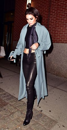 Evening wear: The 20-year-old added a midnight blue silk scarf and a light green loose-fitting long coat, and wore her dark hair twisted up into a topknot