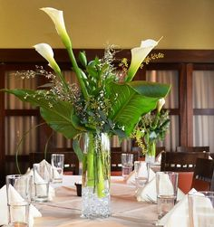 I love tall arrangements like this!  Premium white calla lilies, seeded eucalyptus, Florida ruscus and some awesome tropical foliage (the name of which escapes me at the moment). #centerpiece