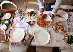 Server maden på hvide tallerkener, brødet i et stykke stof og osten på et skærebræt. En krøllet dug af hør gi'r en afslappet og enkel stemning.