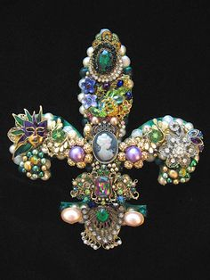 This beautiful Fleur de Lis, Emerald, is hand layered with vintage rhinestone jewelry, earrings, brooches, pearls and more. Made with the green, purples and gold colors of Mardi Gras. What a gorgeous one of a kind home decor with a New Orleans French Quarters flair. Emerald measures 8 x 8 inches. What Makes ArtCreationsByCJ stand apart from other jewelry art:  * HIGH QUALITY. Art Creations are not your typical jewelry art. They are made on a 1/4 wood foundation for sturdiness and extreme…