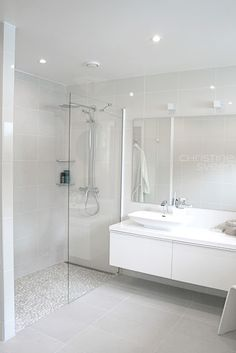 white pebbles for shower and white rectangle large format tiles for walls and square light gray tiles for the floor.