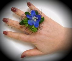 Emma ring fascinator! Corsage not your style? Well try this ring on for size! A delicate combination of blue delphinium, peacock feathers, and deco wire will stay securely on your hand all night! Each ring can be adjusted to fit everyone. boutonnier