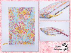 Capa forrada em papel japonês Chiyogami (Yuzen), fundo turquesa, serigrafia com flores de douradas e botão laranja.  Design exclusivo Agenda diária. Tamanho A5 - disponível em A6