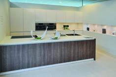 Moderne keuken in hout en matlak. Deze keuken heeft zowel een hoekopstelling als eiland om te koken. De witte keukenkasten zijn opgemaakt in een matlak uitvoering. Het donkere hout van het keukeneiland vormen een mooi contrast met de witte kasten. De hangkasten lopen in lijn van de kasten boven de toestellen. De open regalen zijn voorzien van sfeerverlichting voor het uitstallen van leuke decoratie