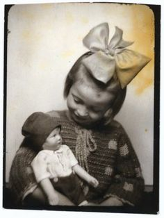 1930s photobooth picture of a little girl with big bow and doll