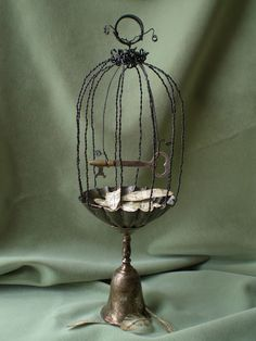 ... a tart tin bird cage. Love the key as a perch....Bell as base...Wow - how creative!