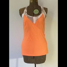 Lucy sports bra work out tank combo. Super cute Lucy sports bra with attached tank in size XS.  Sports bra is very light orange with brown/grey pattern.   Tank is a pretty orange made of lightweight breathable fabric.  Piping on tank is the same pattern as bra.  Adjustable drawstring at bottom of tank. No padding in bra.  Tank has been worn a few times but is in good condition. Lucy Tops Tank Tops