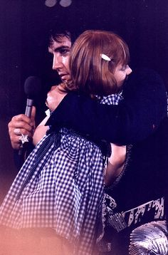 Elvis Hugging Little Girl On Stage 1975 by Marija_:), via Flickr... This little girl is blind and was standing at the end of the stage.. Elvis had His Dr look at her and have some testing done. He paid for her corrective surgery so  she could see....amazing man