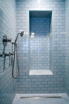 Penny tile flooring from Ann Sacks provides a great size contrast to the larger subway tile look of this sleek, contemporary shower. A built-in nook allows for seating or storage, and a mounted removable shower head can easily be maneuvered in the space.