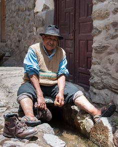 A Kind Old Soul - Ollantaytambo, Peru      As we wandered the charming cobbled backstreets of Ollantaytambo, we came across this man cleaning his shoes in the original Incan aqueduct outside his home.  As we approached he looked up from his work and gave us a warm smile, so we stopped for a chat and he let us take his photo.  This generosity of spirit and kindness towards strangers, was one of the things we loved most about our travels through Peru.