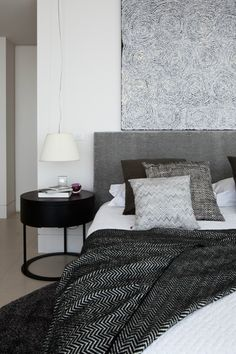 mix of patterns on the bed, black nightstand
