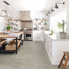 This all-white kitchen looks even fresher with the addition of a light gray floor and a warm wood workspace.