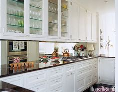 """A mirrored backsplash in a shabby-chic Manhattan apartment gives the illusion of more space. """"The kitchen opens up to the living room on one side and the family room, where we eat and watch TV, on the other,"""" says designer Faye Cone. """"The idea was that it should be an extension of both these spaces."""""""