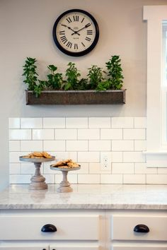Fixer Upper Hosts Chip and Joanna Gaines added new Carrera marble countertops, cabinets, and a subway tile backsplash. The kitchen is staged with cookies on cake stands, fresh herbs in a rustic metal box, and a black and white clock, as seen on HGTV's Fixer Upper. Detail
