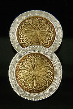 A jazzy pair of cufflinks from the Age of Jazz.  These elegantly designed,  well crafted cufflinks feature 14kt rose gold tops surrounded by white gold borders.  They are decorated with abstract floral designs and geometric motifs.  These jazzy cufflinks were created around 1920 by the jewelry firm Larter & Sons.