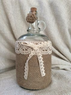 Large decorative bottle, covered with hessian and decorated with lace.
