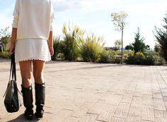 Vestido corto de manga francesa en color crudo, botas altas y maxibolso negro con apliques en plata