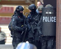 Police are stationed behind a ballistic shield with weapons drawn outside the fire door wh...