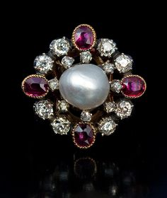 An Antique Pearl, Ruby and Diamond Renaissance Revival Style Ring, circa 1880. The ring features a natural 8.4 mm salt water pearl in an openwork silver topped 18Kt gold bezel. The pearl is surrounded by two rows of gemstones: eight rose cut diamonds, eight old mine diamonds and four rubies. The rubies are set in gold and the diamonds in silver cut-down settings.