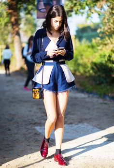Leandra Medine in an a navy blouse, denim shorts, and red oxfords