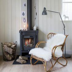 Living room, fireplace, chair with sheepskin, planked walls, hardwood floor //Heerlijke houtkachel