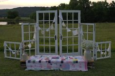 Reclaimed doors and windows used for a backdrop at an outdoor rustic country wedding.