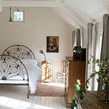 painted brick, shiplap ceilings, iron bed.
