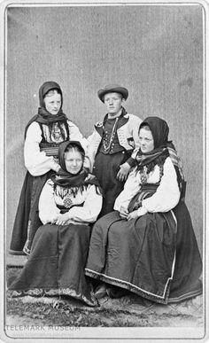 Tre kvinner i beltestakk og ein mann i gråkufte i enkeltfotoatelier.Dei er ukjente. 1870 @ DigitaltMuseum.no