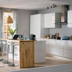 Modern white hi-gloss kitchen from Cooke & Lewis. Contemporary cool can still be comfortable and casual if you team white units with natural-textured accessories, such as a pendant light shade, and add touches of wood for a warm, relaxed Scandi look that's beautiful not bland.