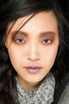 Rodarte (f/w 2014)  LABIOS GLITTER Las hermanas Mulleavy han complementado su colección con un maquillaje a años luz de la discreción. Los ojos se han maquillado con un tono topo que ocupa todo el párpado superior, hasta la ceja, y que cubre también la línea de las pestañas inferiores. Esta mirada siniestra contrasta con los labios lilas con toques de purpurina.