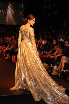 """Karisma Kapoor shows off the sweeping train of the designer gown. Vikram Phadnis' collection was inspired from """"Ponds Gold Radiance"""", and had real gold micro particles. #Bollywood #Style #Fashion #LFW"""