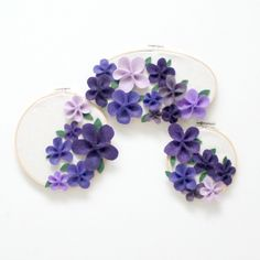 Stunning embroidery hoop art with purple felt flowers.  Love the collage effect.  So pretty!!