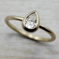 Our new conflict free 6x4mm Pear Solitaire Engagement Ring. It has a low-profile bezel made from eco-friendly recycled metal, with a round (approximately 1.6mm diameter) band. Pictured here in 14k yellow gold and Forever One Moissanite.
