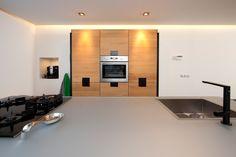 Aanvullend een hoge kastenwand die grotendeels in de muur is geïntegreerd.  De koffienis en indirecte verlichting van het verlaagde plafond maken het tot een functionele en sfeervolle ruimte om te koken en te genieten.