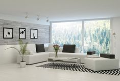 Bright white living room with modern white sofas topped with charcoal pillows stands naturally lit via full height glass panels. Black and white striped area rug and stone brick wall add detail.