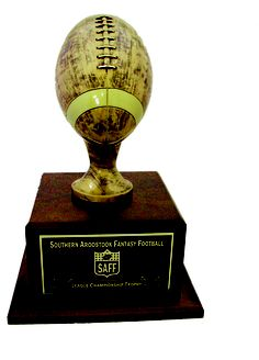 """24 Year Fantasy Football Trophy. This is a 19.5"""" tall Fantasy football trophy. The trophy has a Genuine Walnut Base (12"""" Square) with Bronze Finished Resin Football. Includes header plate personalized with your league info. Comes with 24 individual plates for annual updates. www.rcbawards.com."""