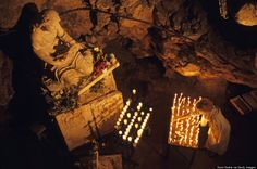 These Mysterious Cave Churches And Monasteries Totally Rock. France, Provence, Sainte-Baume Mountain: woman burning candle at Troglodyte Sainte-Marie Madeleine Holy Cave.
