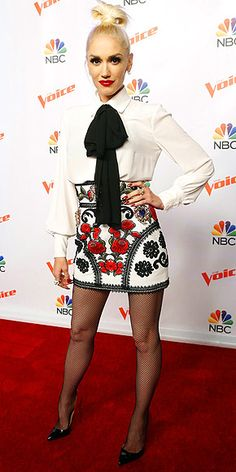 Gwen Stefani in an embroidered mini skirt, bow-topped blouse, fishnets, and heels (and check out that topknot!)